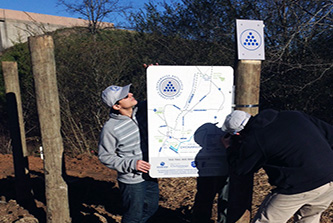Institute of Government creative design specialists Dan Shinkle and Clark Stancil install directional signs with UGA College of Environment and Design Associate Professor Doug Pardue on the new Chickamauga Battlefield Connector Trail under U.S. Highway 27.